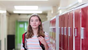 Retrato do estudante fêmea Walking Down Corridor e sorriso da High School na câmera filme