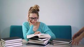 Retrato do estudante inteligente com livro aberto que lê o na biblioteca de faculdade vídeos de arquivo