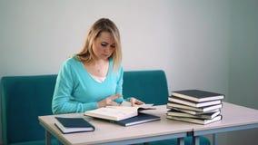 Retrato do estudante inteligente com livro aberto que lê o na biblioteca de faculdade filme