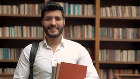 Retrato do estudante masculino na biblioteca video estoque