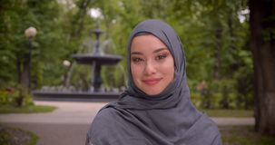 Retrato do estudante mu?ulmano sonhador no hijab que olha os arredores que sorri na c?mera no parque com uma fonte vídeos de arquivo