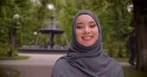 Retrato do estudante muçulmano sonhador no hijab que sorri na posição da câmera na frente da fonte vídeos de arquivo