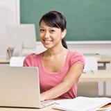 Retrato do estudante que senta-se na mesa na sala de aula Fotografia de Stock