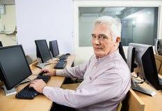 Retrato do estudante superior seguro Sitting At Desk em Classroo foto de stock