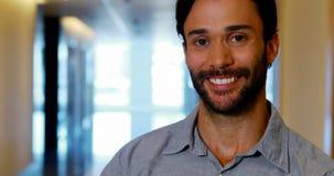 Retrato do executivo masculino que está no corredor video estoque
