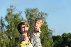 Retrato do filho feliz do beijo e da agitação da mamã no jardim verde do verão Bebê de abraço da mãe bonito que olha a câmera Imagem de Stock