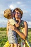 Retrato do filho feliz do beijo e da agitação da mamã no jardim verde do verão Bebê de abraço da mãe bonito que olha a câmera Imagens de Stock