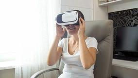Retrato do filme de observação de sorriso da jovem mulher em auriculares de VR Foto de Stock Royalty Free