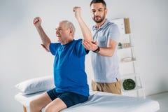 retrato do fisioterapeuta focalizado que faz a massagem ao homem superior fotografia de stock