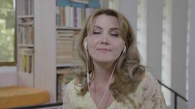 Retrato do fone de ouvido vestindo da mulher bonita nova que escutam a música ou do audiobook que relaxa em casa em férias de ver vídeos de arquivo