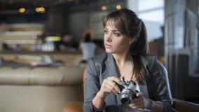 Retrato do fotógrafo novo do adolescente com cabelo longo no t-shirt preto no café Menina bonita que guarda a câmera análoga velh Imagem de Stock Royalty Free