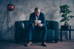 Retrato do gerente superior vestindo do terno do revestimento do indivíduo ocupado atrativo elegante elegante agradável que senta imagem de stock