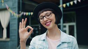 Retrato do gesto de mão bonito da APROVAÇÃO da exibição da jovem mulher que sorri fora filme