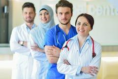 Retrato do grupo feliz seguro de doutores que estão no escritório médico fotografia de stock