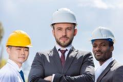 Retrato do grupo multiethic de arquitetos profissionais nos capacetes de segurança Foto de Stock Royalty Free