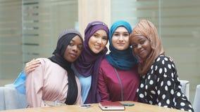 Retrato do grupo multirracial de mulheres muçulmanas vestidas nos vestidos nacionais que levantam no centro de compra vídeos de arquivo