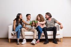 Retrato do grupo novo de amigos que sentam-se em um sofá em um estúdio, garrafas do tinido fotografia de stock royalty free