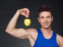 Retrato do halterofilista de sorriso novo que guarda a maçã Imagem de Stock Royalty Free