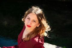 Retrato do Headshot de uma menina loura na propaga??o clara natural ao longo do banco de um rio imagem de stock