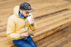Retrato do homem à moda com o tampão vestindo da barba, o revestimento amarelo e as calças de brim bebendo o café delicioso e esc Fotografia de Stock Royalty Free