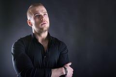 Retrato do homem à moda considerável na camisa preta elegante que olha acima no futuro seriamente Com espaço da cópia Fotos de Stock