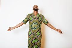 Retrato do homem africano considerável novo que veste gesticular de sorriso do traje nacional verde-claro Foto de Stock