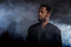 Retrato do homem africano novo consider?vel no fundo preto imagem de stock royalty free