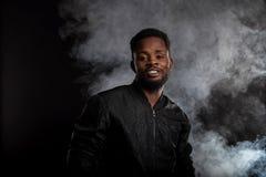 Retrato do homem africano novo consider?vel no fundo preto imagem de stock