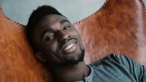 Retrato do homem africano que senta-se na cadeira, sorrindo e olhando em linha reta na câmera O homem olha sonhador, pensativo e  fotografia de stock