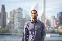 Retrato do homem afro-americano considerável novo com skyline de NYC fotografia de stock royalty free