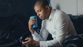 Retrato do homem afro-americano ocupado que usa um smartphone e bebendo o café em um café moderno vídeos de arquivo