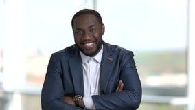Retrato do homem alegre do africano negro no terno que está no escritório filme