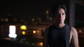 Retrato do homem asiático considerável novo que pensa fora na noite vídeos de arquivo