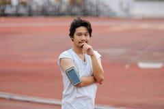 Retrato do homem asiático da aptidão nova que olha a câmera e a posição na trilha no estádio Foto de Stock