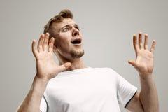 Retrato do homem assustado no cinza foto de stock