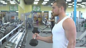 Retrato do homem atlético forte no treinamento do gym o halterofilista faz um exercício no bíceps com pesos vídeos de arquivo