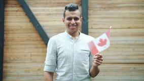 Retrato do homem atrativo da raça misturada que guarda a bandeira canadense que sorri fora filme