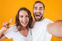 Retrato do homem atrativo e da mulher de dois povos que sorriem ao tomar a foto do selfie, isolado sobre o fundo amarelo fotos de stock
