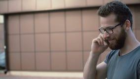 Retrato do homem atrativo novo com barba e dos vidros que andam na rua, usando o smarphone Indivíduo que fala pelo telefone filme