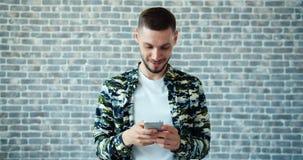 Retrato do homem atrativo que joga o jogo de vídeo na tela de toque do smartphone vídeos de arquivo