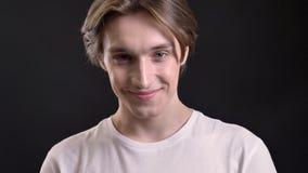 Retrato do homem bonito novo na camisa branca que sorri in camera, fundo preto, menino encantador com riso dos olhos azuis video estoque
