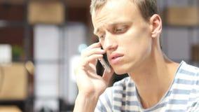 Retrato do homem cansado que fala no telefone, discutindo a edição no telefone video estoque