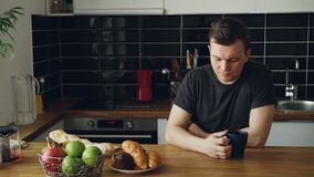 Retrato do homem caucasiano novo que senta-se na tabela na cozinha espaçoso moderna, olhando através da janela, chá bebendo, é video estoque