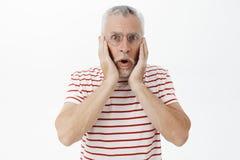 Retrato do homem chocado que olha surpreendido e excitado na câmera com a maxila deixada cair que mantém as mãos pressionadas em  fotos de stock