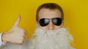 Retrato do homem com barba branca e emoção engraçada e alegremente humana dos vidros pretos, polegares acima, na parede amarela vídeos de arquivo
