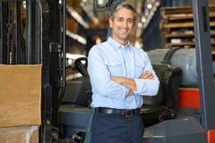 Retrato do homem com o caminhão de empilhadeira no armazém Imagem de Stock