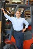 Retrato do homem com o caminhão de empilhadeira no armazém Imagens de Stock
