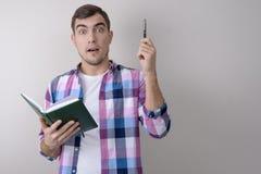 Retrato do homem com pena e do caderno no fundo cinzento imagens de stock
