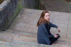 Retrato do homem com uma barba longa e de um cabelo longo no stairca Imagens de Stock