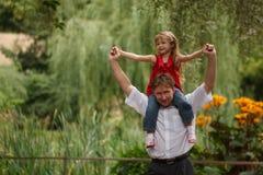 Retrato do homem com uma filha no jardim do verão Fotografia de Stock Royalty Free